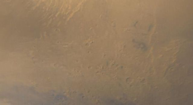 NASA's Mars Global Surveyor shows a frosty, retreating south polar cap (white) on Mars, and wisps of dust storm clouds (grayish-orange). Also seen is the southern most of the large environmental changes volcanoes, Arsia Mons.