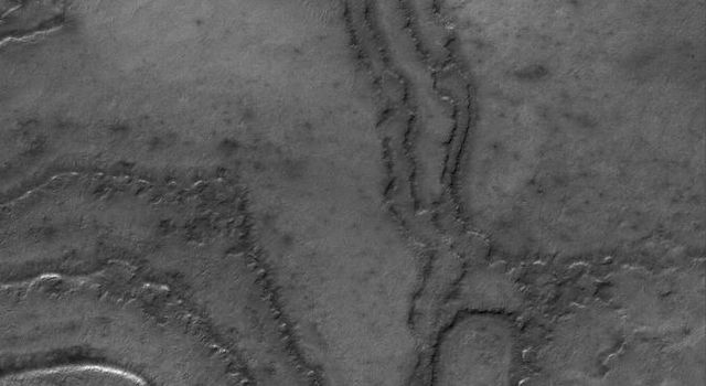 NASA's Mars Global Surveyor shows layering in terrain at the high southern latitudes of Mars. South polar layers are commonly assumed to consist of varying amounts of dust and ice.