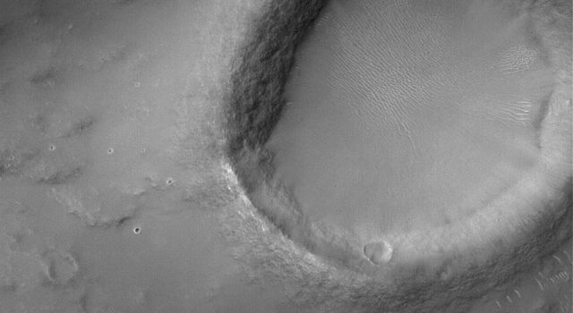 NASA's Mars Global Surveyor shows a crater that in south central Syrtis Major Planum on Mars. The image also captures a portion of the light-toned wind streak formed in the lee (to the left) of the crater. A wind streak is also present.