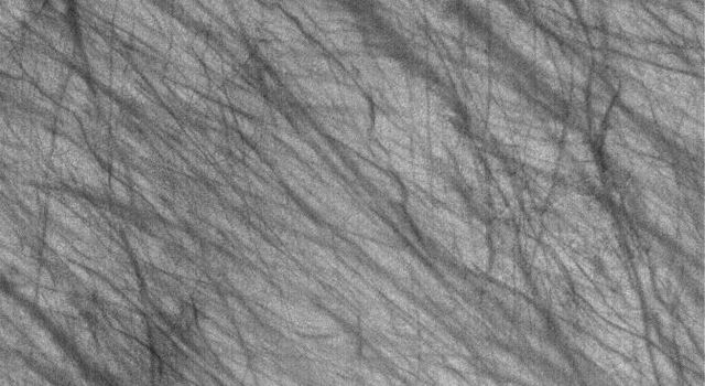 This image from NASA's Mars Global Surveyor shows dark streaks on a plain south of the giant impact basin, Hellas Planitia. The streaks map the routes traveled by dozens of individual southern spring and early summer dust devils.
