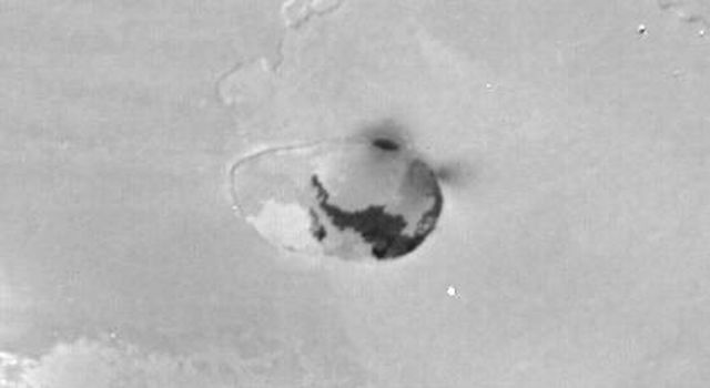 NASA's Voyager 1 took this narrow-angle camera image on 5 March 1979 from a distance of 69,000 kilometers. The feature shown is a volcanic caldera which may be actively spewing material into space (dark gray fuzz near upper-right part of the caldera rim).