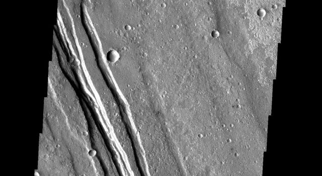 The linear features in this image are called graben and are formed when two parallel faults have a downdropped block of material between them. These graben are located between Syria Planum and Claritas Rupes as seen by NASA's 2001 Mars Odyssey.