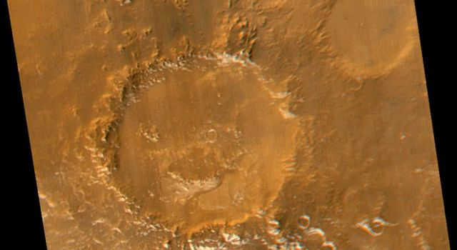This image captured by NASA's Mars Global Surveyor (MGS) in 2005 shows 'Galle Crater' or the 'Happy Face Crater' with patches of white water ice frost in and around the crater's south-facing slopes.