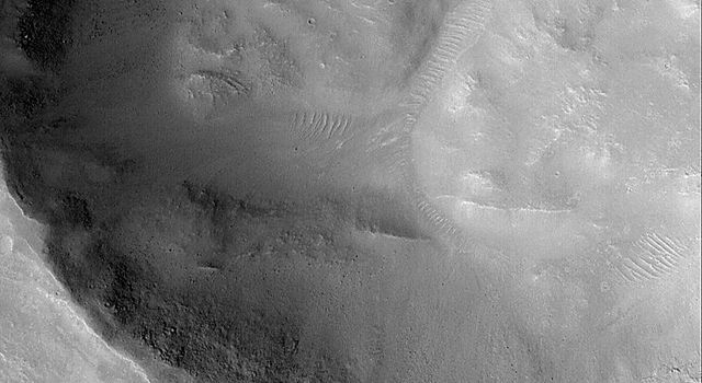 NASA's Mars Global Surveyor shows wide impact crater on the floor of a larger crater in the Nepenthes Mensae region on Mars.