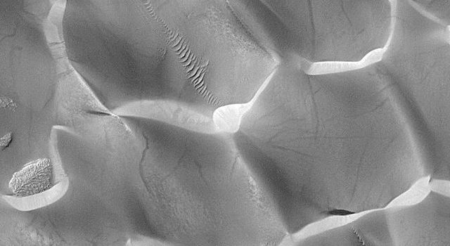 NASA's Mars Global Surveyor shows dark streaks on the steep, down-wind slopes of sand dunes in Rabe Crater on Mars.