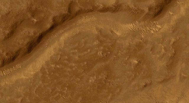 NASA's Mars Global Surveyor shows an intermountain valley floor in the Libya Montes region of Mars. The Libya Montes were formed by the giant impact that created the ancient Isidis basin.