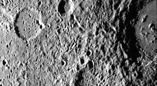 Cratered terrain very similar to that on the Moon is shown in this TV photo of Mercury taken by NASA's Mariner 10. Numerous small craters and linear grooves radial to the crater can be seen.