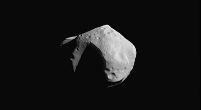 This image of asteroid 253 Mathilde was returned by NASA's NEAR Shoemaker spacecraft on June 27, 1997. The shadowed, wedge-shaped feature at the lower right is another large crater viewed obliquely.