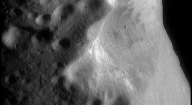 This image from NASA's NEAR Shoemaker shows an oblique view of Eros' large central crater. Brightness or albedo patterns on the walls of this crater are evident as are boulders inside this crater and the smaller nearby craters.