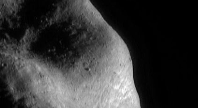 This image of asteroid Eros, taken by NASA's NEAR Shoemaker on March 6, 2000, shows the southwestern part of the saddle region with fragments of Eros' native rock, shattered over the eons by formation of impact craters.
