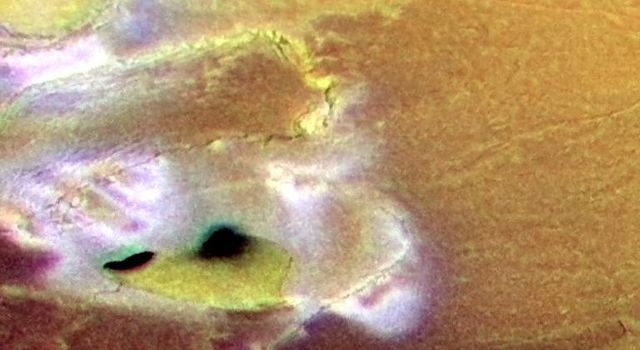 Volcanic calderas, lava flows and cliffs are seen in this false color image of a region near the south pole of Jupiter's volcanic moon Io, created by combining a black and white image taken by NASA's Galileo spacecraft with lower resolution color images.