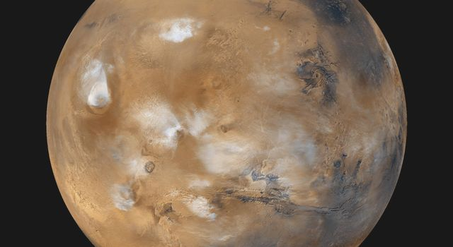 Twelve orbits a day provide NASA's Mars Global Surveyor MOC wide angle cameras a global 'snapshot' of weather patterns across the planet. Here, bluish-white water ice clouds hang above the Tharsis volcanoes.