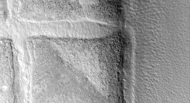 NASA's Mars Global Surveyor shows a circle of mounds on the northern plains near the Phlegra Montes on Mars. These mounds were once the rim of a crater formed by impact of a meteorite.