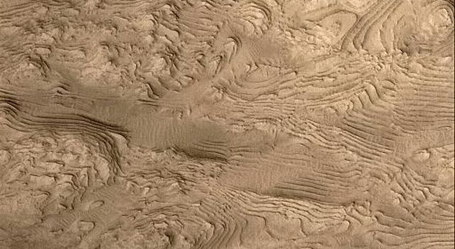 NASA's Mars Global Surveyor shows layered material in west Arabia Terra crater on Mars.