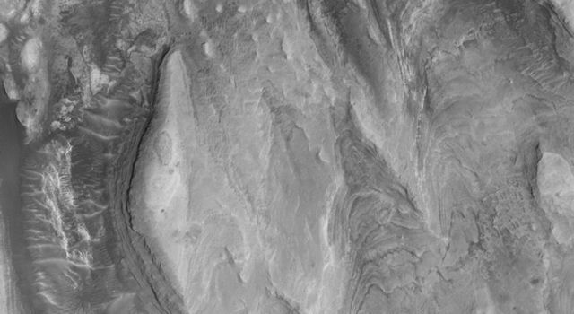 NASA's Mars Global Surveyor shows layered material in Gale Crater interpreted to be sedimentary rock on Mars that are quite thick and reveal a complex history of change.