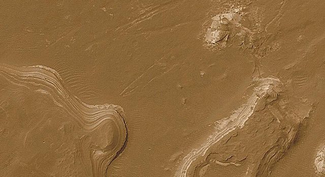 NASA's Mars Global Surveyor shows layered outcrops in craters and chasms in Gale Crater on Mars seen as stair-stepped series of cliffs and benches composed of similar materials with similar thicknesses.