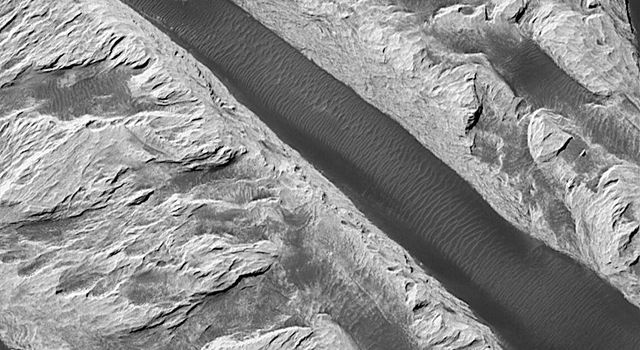 NASA's Mars Global Surveyor shows a ridged mound that was first seen and informally named 'White Rock' located in Pollack Crater on Mars.