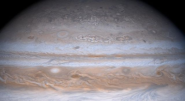 The familiar banded appearance of Jupiter at low and middle latitudes gradually gives way to a more mottled appearance at high latitudes in this striking true color image taken Dec. 13, 2000, by NASA's Cassini spacecraft.