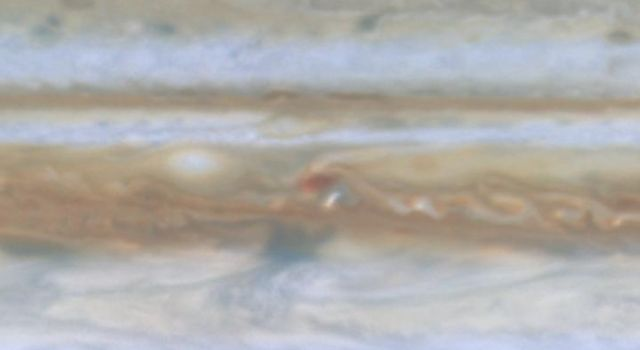 Taken by NASA's Cassini spacecraft, a small white spot, probably a thunderstorm, lies to the south of a larger, brown spot on Jupiter.