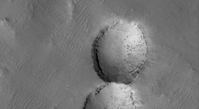 This image from NASA's Mars Global Surveyor shows a portion of a pit chain on the lower, northern flank of the giant martian volcano, Arsia Mons.