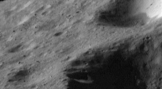 This image of asteroid Eros, taken by NASA's NEAR Shoemaker on May 2, 2000, shows a view toward Eros' horizon with variations in the brightness of material on the walls of the craters; and a scattering of boulders.