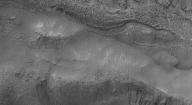NASA's Mars Global Surveyor shows two suites of gullies within a single impact crater in the Terra Cimmeria region of Mars. Gully erosion has cut into the layered rock exposed on the crater wall.