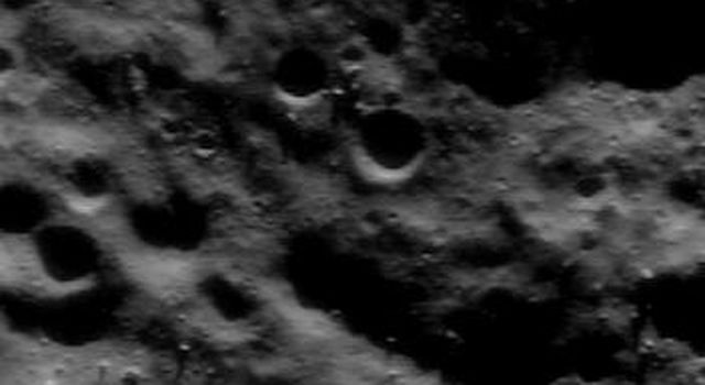 This image of asteroid Eros, taken by NASA's NEAR Shoemaker on June 6, 2000, shows a landscape textured by low ridges and grooves running from left to right, with numerous boulders sprinkled on them.