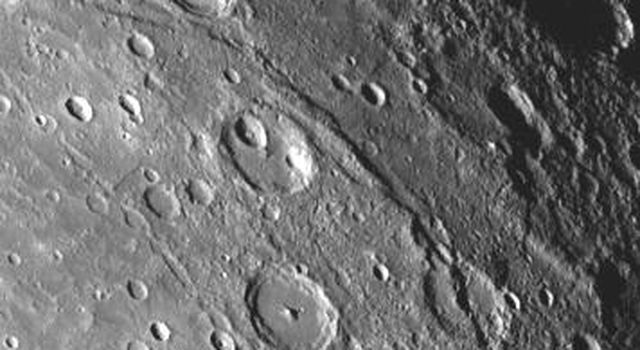 A scarp, or cliff, extends diagonally from upper left to lower right in this picture of Mercury taken by NASA's Mariner 10. The structures are believed to be formed by the compressive forces due to crustal shortening.