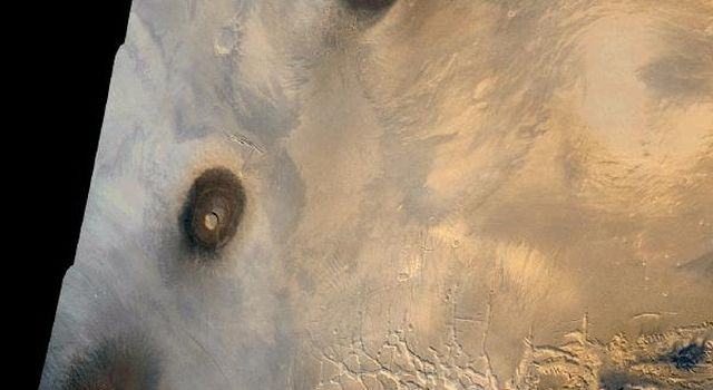 NASA's Viking 1 Orbiter color mosaic of the eastern Tharsis region on Mars. At left, from top to bottom, are the three 25 km high volcanic shields, Ascraeus Mons, Pavonis Mons, and Arsia Mons.