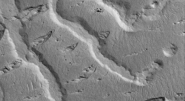 NASA's Mars Global Surveyor shows the inverted remains of several channels in a fan-like complex in the Aeolis region of Mars. The inverted channels are flat-topped ridges that trend from southeast to northwest.