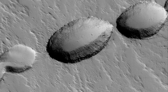 NASA's Mars Global Surveyor shows a chain of collapse pits on the lower south flank of Ascraeus Mons on Mars. Pit chains such as this are the result of collapse along fault lines.