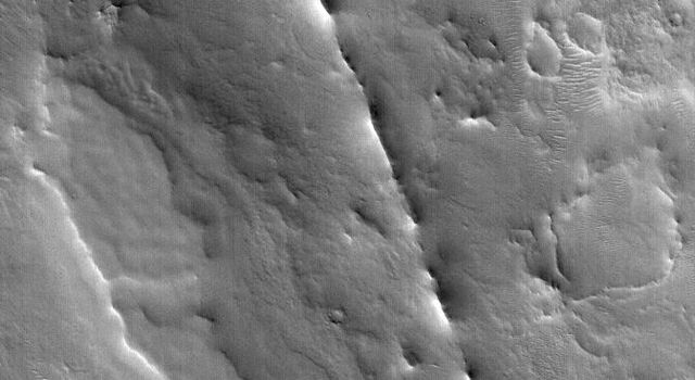 NASA's Mars Global Surveyor shows a dike exhumed by erosion from beneath the cratered terrain near Auqakuh Vallis in northeastern Arabia Terra on Mars.