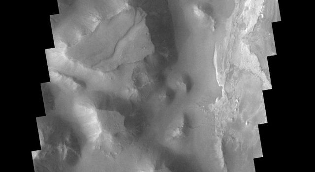 This image captured by NASA's 2001 Mars Odyssey spacecraft shows a small portion of Iani Chaos on Mars. The brighter floor material is being covered by sand, probably eroded from the mesas of the Chaos.