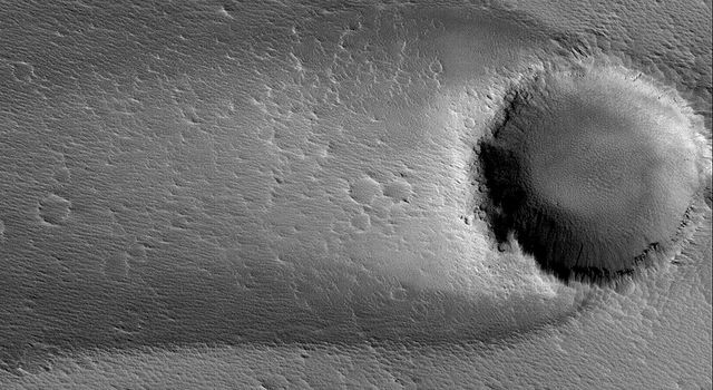 NASA's Mars Global Surveyor shows  a wind streak formed in the lee of an impact crater in western Daedalia Planum on Mars.