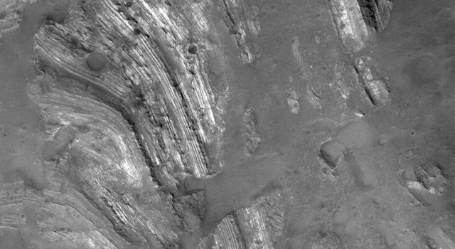 NASA's Mars Global Surveyor shows outcrops of light-toned, layered rock exposed in the central peak of Oudemans Crater, near the Labyrinthus Noctis of the western Valles Marineris complex on Mars.