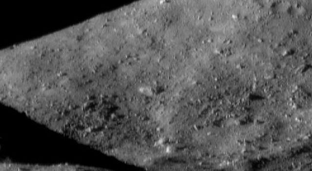 This image of asteroid Eros, taken by NASA's NEAR Shoemaker on Dec. 19, 2000, shows a surface packed with boulders. A low ridge in the foreground (bottom) casts a wedge-shaped shadow against the hill in the background.