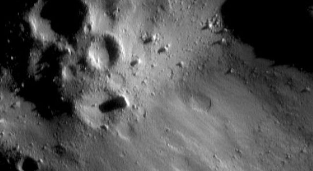 This image of asteroid Eros, taken by NASA's NEAR Shoemaker on Jan. 7, 2001, shows surfaces with typical rounded craters and large boulders. An abruptly edged swath extending is remarkably more smooth, subdued, and lacking in small-scale detail.