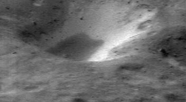 This image of asteroid Eros, taken by NASA's NEAR Shoemaker on Jan. 11, 2001, shows material on the inner wall of a crater, brighter than the surrounding regolith and is thought to be subsurface material exposed when overlying, darker regolith slides off.