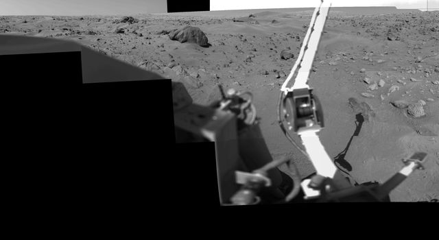 This image was taken by NASA's Viking Lander 1 at Chryse Planitia on Mars. The lander can be seen in the foreground looking toward the rugged martian terrain.