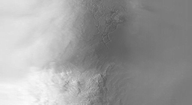 NASA's Mars Global Surveyor shows a large dust-raising event that occurred on July 8, 2001, as cold, raging winds blew off the frozen south polar cap and rushed toward the network of troughs known as Labyrinthus Noctis near the martian equator.