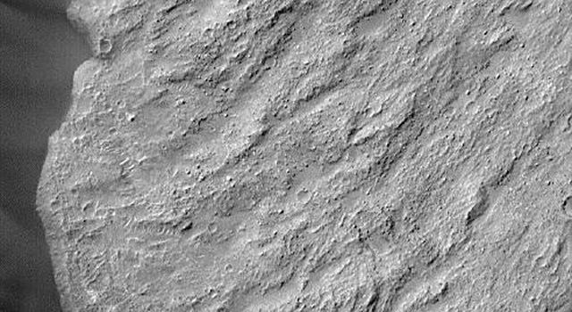 NASA's Mars Global Surveyor shows shear striations, dark dunes banked up against the toe of the slide and over-riding light-toned ripples and boulders on the toe of Ganges Chasma on Mars.
