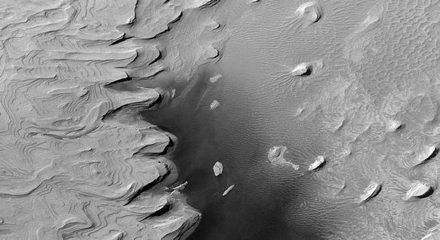 NASA's Mars Global Surveyor shows layered rock outcrops reaching deep down into the martian crust in the walls of the Valles Marineris.