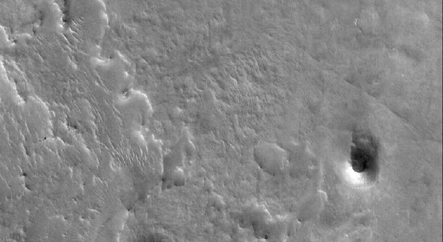 NASA's Mars Global Surveyor shows  two small mesas, a hill, and other landforms in the highly-eroded landscape of eastern Arabia Terra on Mars.