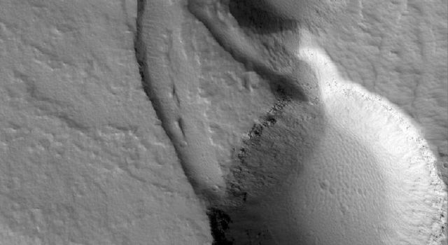 NASA's Mars Global Surveyor shows collapse pits on the lower east flank of Ascraeus Mons, a larger volcano in the Tharsis region of Mars.