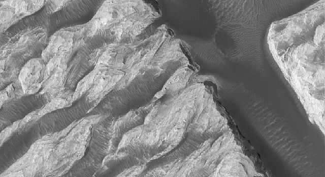 NASA's Mars Global Surveyor shows a portion of the famous 'White Rock' feature in Pollack Crater in the Sinus Sabaeus region of Mars. Dark materials in this image include sand dunes and large ripples.