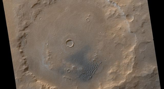 NASA's Mars Global Surveyor shows dark-gray or blue-black sand shaded with light-toned frosted dunes in Kaiser Crater on Mars.