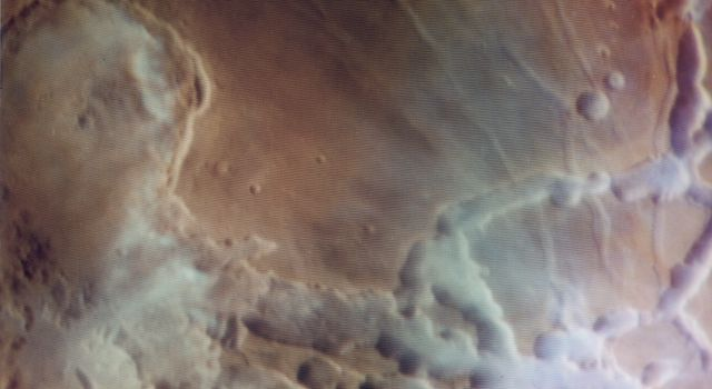 NASA's Viking Orbiter 1 captured the sun rising over Noctis Labyrinthus (the labyrinth of the night), bright clouds of water ice can be observed in and around the tributary canyons of this high plateau region of Mars.