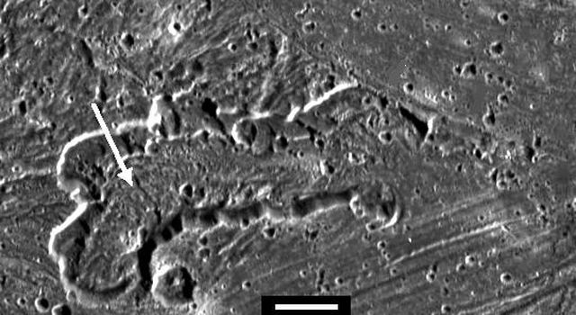 An irregularly shaped caldera, or pit, within the bright swath called Sippar Sulcus on Jupiter's moon Ganymede dominates this image taken by NASA's Galileo spacecraft.
