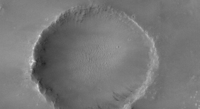 NASA's Mars Global Surveyor shows an old meteor impact crater, somewhat filled with sediment. This crater is located near a larger crater, Newcomb, in far northern Noachis Terra on Mars.