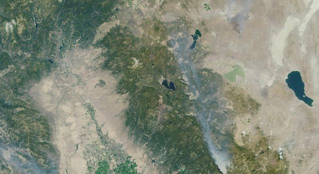 These images from NASA's Terra satellite are of the Central Valley and the Sierra Nevada Mountains showing several smoke plumes from wildfires burning throughout Northern California on August 13, 2001.